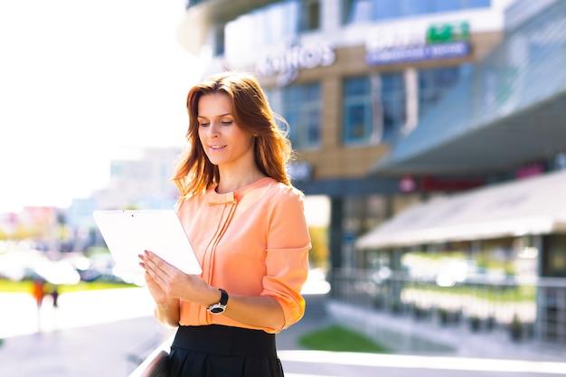 Portret ładnej bizneswoman w eleganckim stylu casual przy użyciu cyfrowego tabletu na zewnątrz