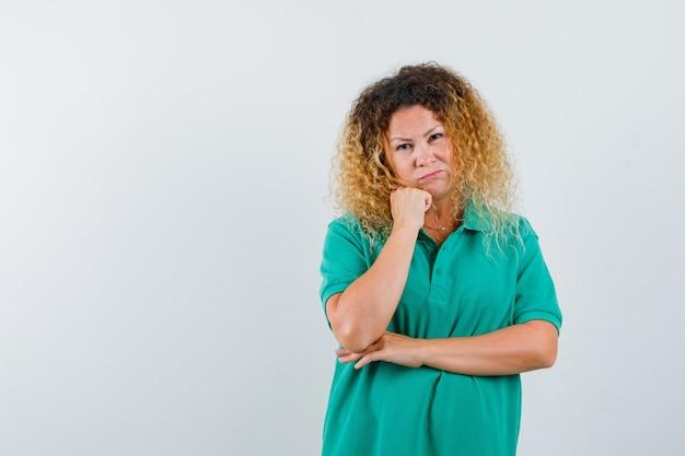 Portret ładnej blond pani podpierając brodę pod ręką w zielonej koszulce polo i patrząc rozczarowany widok z przodu