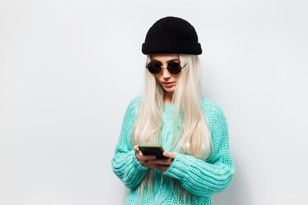 Portret ładnej blondynki przy użyciu smartfona