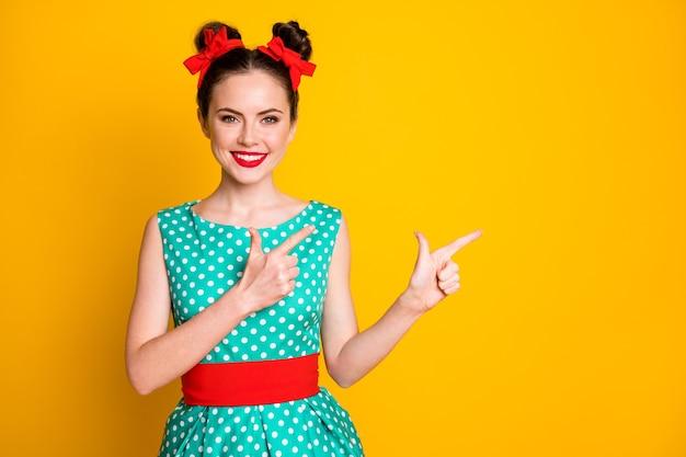 Portret ładnej, całkiem wesołej dziewczyny, wskazującej dwa palce wskazujące na bok, na białym tle nad żywym żółtym kolorem tła