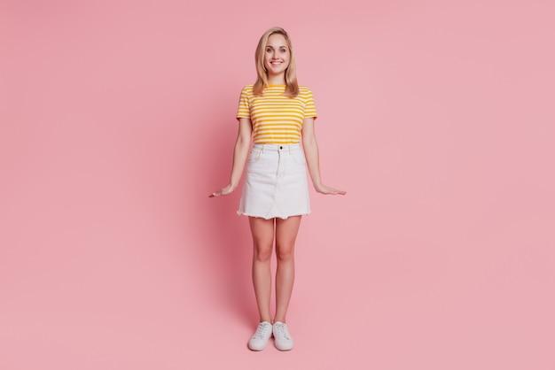 Portret ładnej dziewczęcej damy pozującej nieśmiało na różowym tle