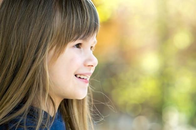 Portret ładnej dziewczynki o szarych oczach i długich jasnych włosach, uśmiechającej się na zewnątrz