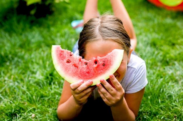 Portret ładnej dziewczyny jedzącej kawałek arbuza na trawie w ogrodzie.