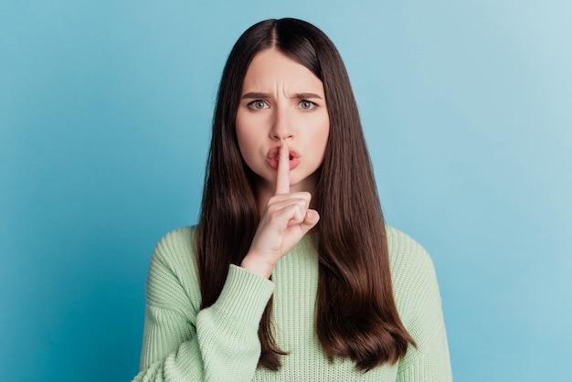 Portret ładnej dziewczyny, która zakrywa usta palcem, prosząc, abyś był cicho, pozując na turkusowej ścianie