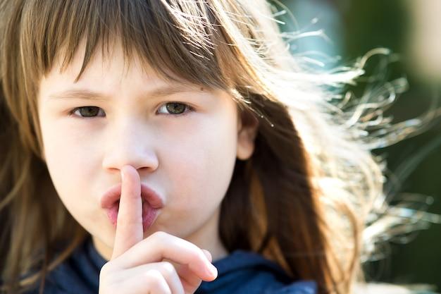 Portret ładnej dziewczyny mienia palec na jej wargach z cichym westchnieniem
