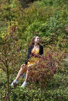 Portret ładnej dziewczyny mody w pobliżu jesiennego buszu, ciesz się naturą