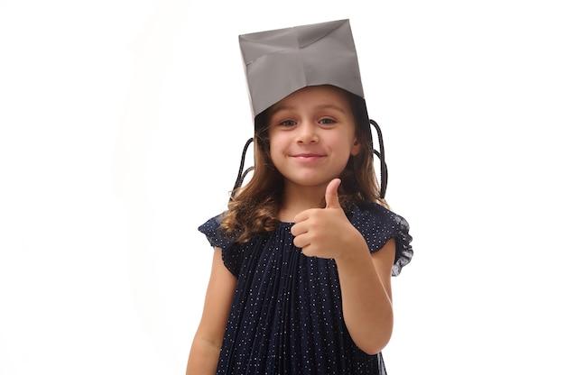 Portret ładnej dziewczyny rasy kaukaskiej zabawy, kładąc na głowie czarny pakiet zakupów, uśmiechając się patrząc w kamerę, pokazując kciuk do góry, na białym tle, kopia przestrzeń. koncepcja czarnego piątku