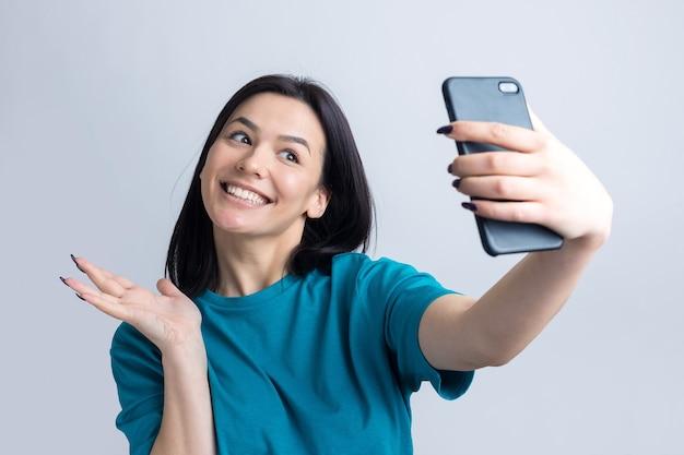Portret ładnej dziewczyny robiącej selfie na białym tle na szarym tle