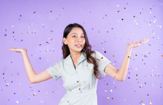 Portret ładnej dziewczyny stojącej pod kupowaniem konfetti z okazji świętowania, odizolowanej na fioletowym tle