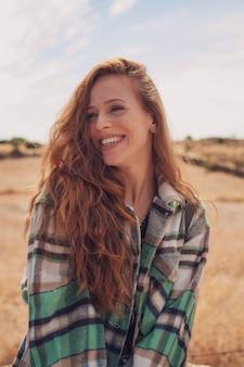Portret ładnej dziewczyny uśmiechając się do kamery z polem w jej tle