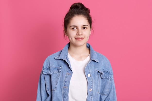 Portret ładnej dziewczyny z kok w dżinsowej kurtce i białej koszulce z delikatnym uśmiechem na różu