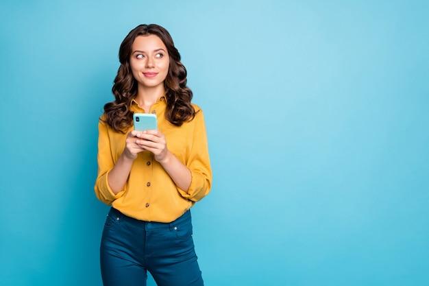 Portret ładnej falistej kobiety trzymającej telefon za ręce, myśląc nad pomysłem na tekst postu, patrząc z boku na puste miejsce, nosić żółte spodnie koszuli.