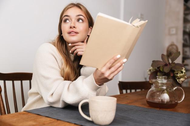 Portret ładnej kaukaskiej kobiety noszącej zwykłe ubrania, czytającej książkę i pijącej herbatę w przytulnym pokoju