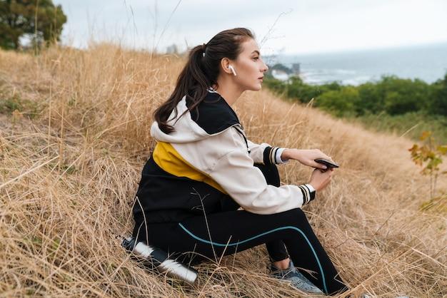 Portret ładnej kaukaskiej kobiety w odzieży sportowej, korzystającej ze słuchawek i smartfona, siedząc na suchej trawie nad brzegiem morza