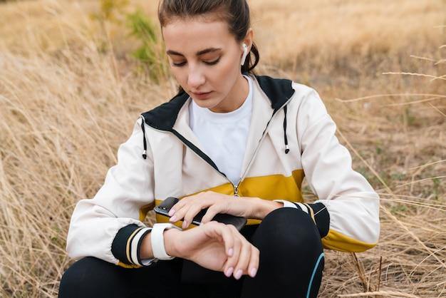 Portret ładnej kaukaskiej kobiety w odzieży sportowej korzystającej ze słuchawek i smartwatcha, siedząc na suchej trawie