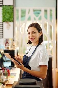 Portret ładnej kobiety baristy pracującej na komputerze typu tablet i uśmiechającej się do kamery