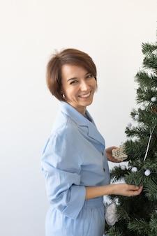 Portret ładnej kobiety dekorującej choinkę