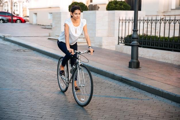 Portret ładnej kobiety na rowerze na ulicy miasta