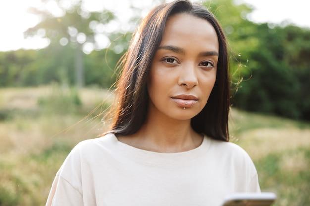 Portret ładnej kobiety noszącej piercing do ust, patrzącej na kamerę i trzymającej smartfon w zielonym parku