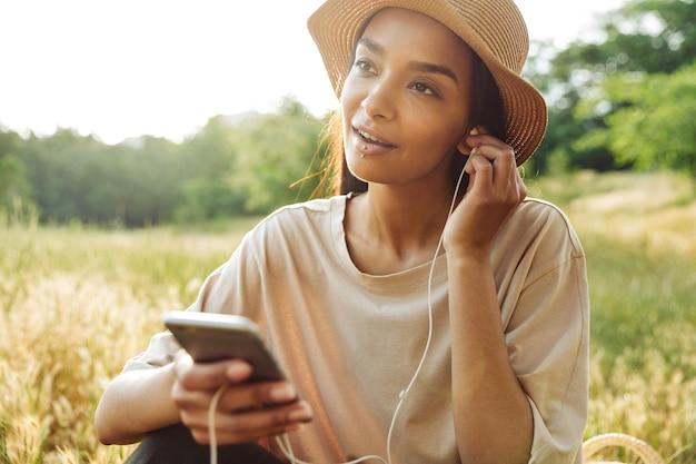 Portret ładnej kobiety noszącej przekłuwanie warg i słomkowy kapelusz słuchającej muzyki na smartfonie siedzącej na trawie w zielonym parku