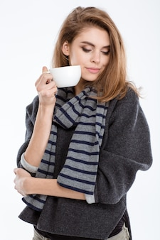 Portret ładnej kobiety stojącej z filiżanką kawy na białym tle