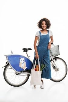 Portret ładnej kobiety trzymającej torbę na zakupy, stojąc nad rowerem na białym tle nad białą ścianą