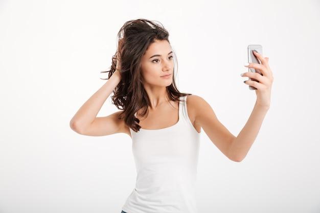 Portret ładnej kobiety ubranej w podkoszulek przy selfie