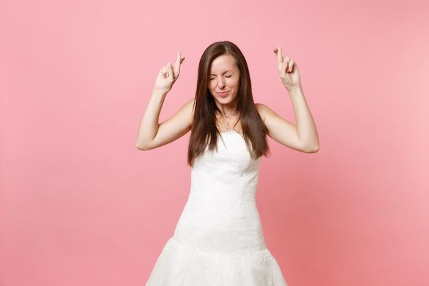 Portret ładnej kobiety w białej sukni czekającej na wyjątkowy moment, trzymającej kciuki, zamknięte oczy eyes