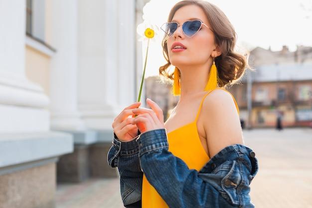Portret ładnej kobiety w okularach przeciwsłonecznych w kształcie serca, trzymającej kwiat przed słońcem, słoneczny letni dzień, stylowa odzież, trend w modzie, niebieska kurtka jeansowa, żółta sukienka, eleganckie kolczyki boho hipster