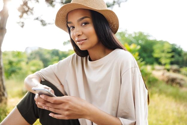 Portret ładnej kobiety w przekłuciu ust i słomkowym kapeluszu, trzymającej smartfona siedzącego na ławce w zielonym parku