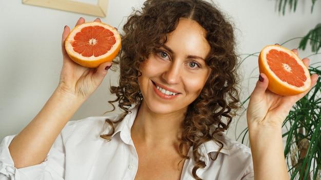 Portret ładnej kobiety w średnim wieku z kręconymi włosami z grejpfrutem w domu - jasny pokój. pojęcie szczęścia, piękna i zdrowia
