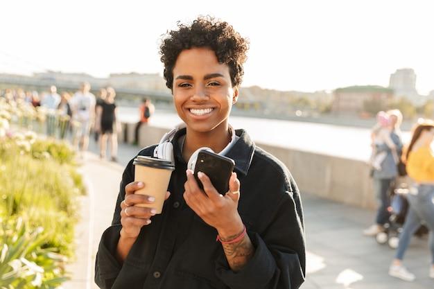 Portret ładnej kobiety z kręconą fryzurą afro trzymającą smartfona podczas spaceru wzdłuż brzegu rzeki