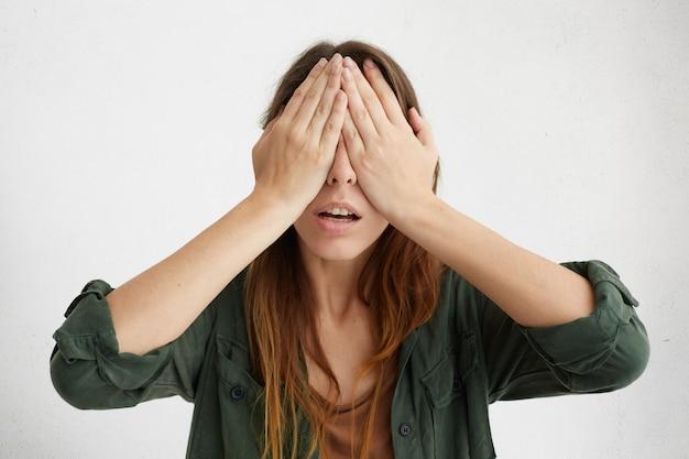 Portret ładnej kobiety zasłaniając oczy rękami. młoda zdesperowana kobieta, która ukrywa twarz, nie chcąc nikogo widzieć.