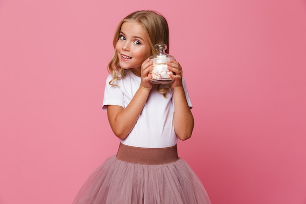 Portret ładnej małej dziewczynki mienia słój marshmallow