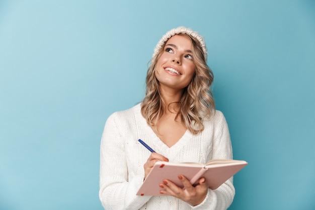 Portret ładnej marzącej kobiety w czapce z dzianiny, uśmiechającej się i robiącej notatki w pamiętniku