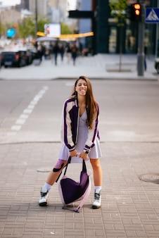 Portret ładnej młodej kobiety bawiącej się na ulicy