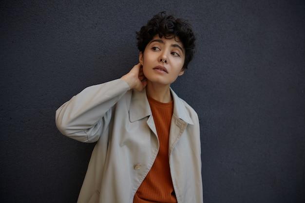 Portret ładnej młodej kręconej kobiety z krótkimi fryzurami, ubrana w modną beżową odzież wierzchnią i lśniący sweter, podczas gdy pozuje na zewnątrz nad czarną betonową ścianą, trzymając rękę na szyi i patrząc na bok