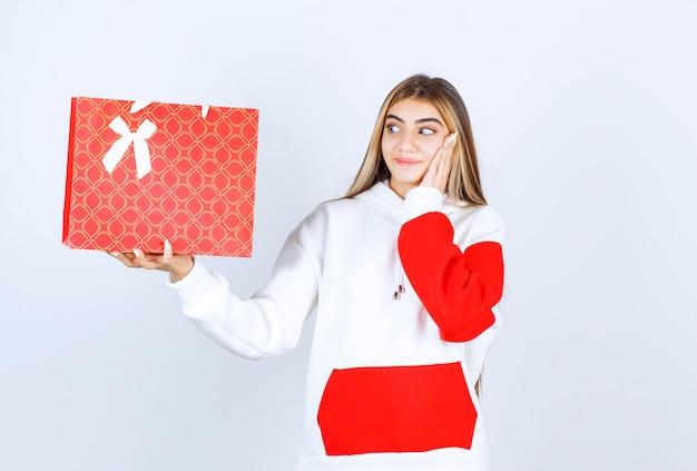 Portret ładnej modelki stojącej i pokazującej torbę na prezent