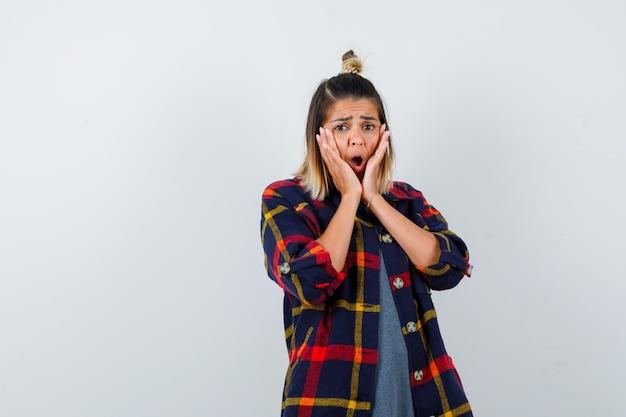 Portret ładnej pani trzymającej ręce przy ustach w casualowej koszuli i patrzącej na przerażony widok z przodu