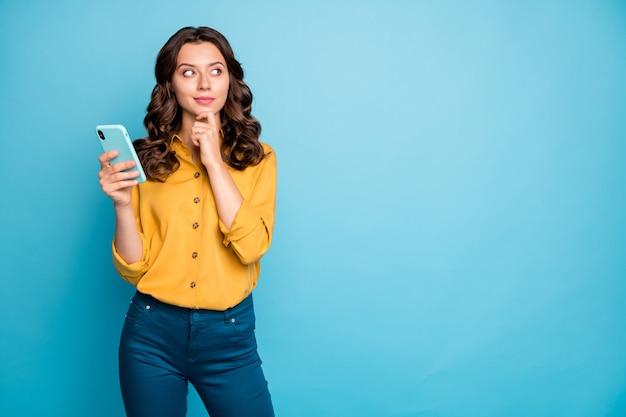 Portret ładnej pani trzymającej telefon za ręce, myśląc nad pomysłem na tekst postu, patrząc na puste miejsce, nosić żółte spodnie koszuli.