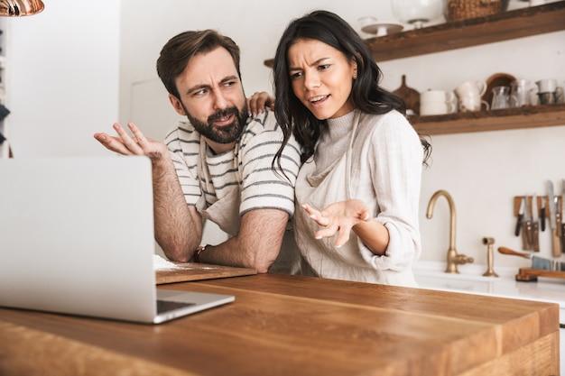 Portret ładnej pary mężczyzny i kobiety w wieku 30 lat w fartuchach, patrząc na laptopa podczas gotowania ciasta w kuchni w domu