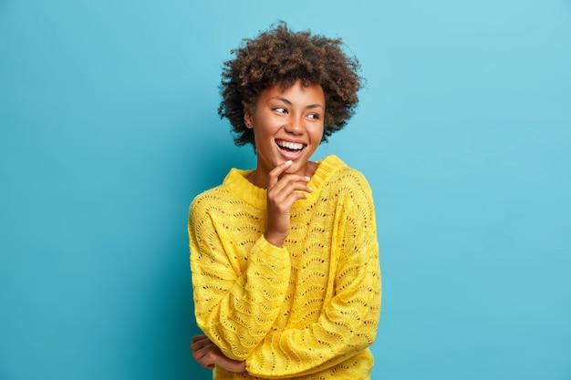 Portret ładnej, przyjemnie wyglądającej, wesołej kobiety, radośnie się śmieje, ma szeroki uśmiech i idealne białe zęby, dobry nastrój, beztroski wyraz twarzy ubrana niedbale pozuje na niebieskiej ścianie