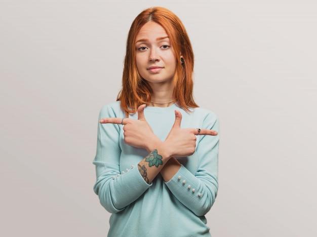 Portret ładnej rudej dziewczyny wątpiącej między dwiema rzeczami