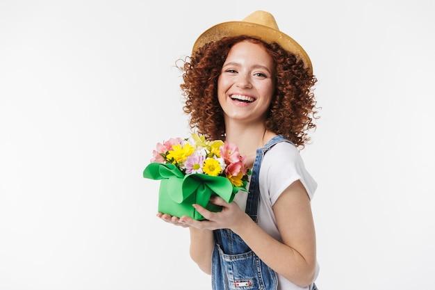 Portret ładnej rudowłosej kręconej kobiety 20 lat w letnim słomkowym kapeluszu uśmiecha się i trzyma pudełko na kwiaty izolowane nad białą ścianą