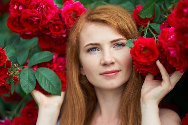 Portret ładnej rudowłosy dziewczyny ubrane w białą sukienkę na tle kwitnących róż