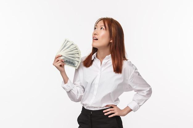 Portret ładnej udanej azjatyckiej kobiety w białej koszuli, bizneswoman zmęczony byciem bogatym, machający pieniędzmi próbującymi się ochłodzić, spojrzał z ulgą, stał się bogaty na białej ścianie