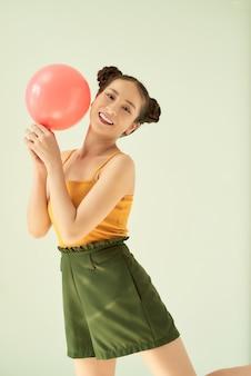 Portret ładnej, uroczej, uroczej, atrakcyjnej, uroczej, wesołej, wesołej pozytywnej dziewczyny trzymającej balon powietrzny