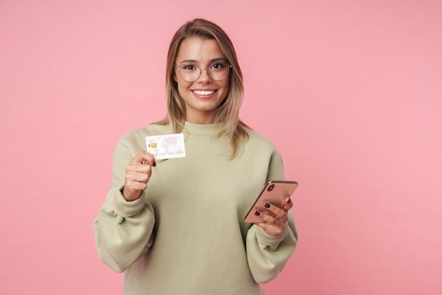 Portret ładnej uśmiechniętej kobiety w okularach trzymającej telefon i kartę kredytową na białym tle nad różową ścianą