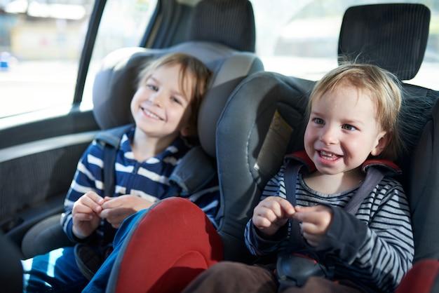 Portret ładni chłopiec siedzi w samochodowych siedzeniach. bezpieczeństwo transportu dzieci
