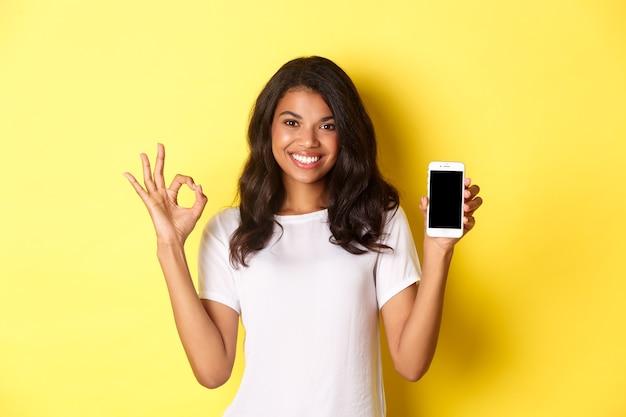 Portret ładnie wyglądającej afrykańskiej dziewczyny w białej koszulce pokazującej znak porządku i aplikacji na smartfona st...